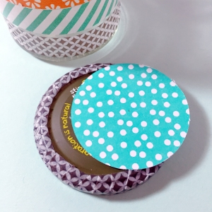Measure the diameter of the lid (the part not covered by the Washi tape) and cut a circle to cover this, from patterned paper. Stick this on with PVA glue.
