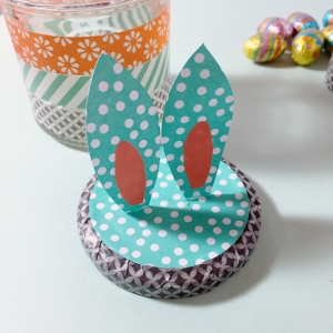Cut two rabbit ear shapes from patterned paper and stick these on with the glue gun by gluing the bottom edge to make them stand upright.
